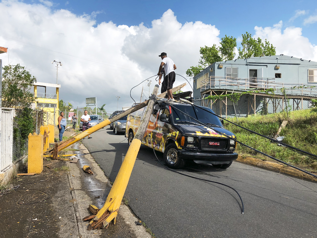 Van with electric pole on top of it in Puerto Rico after Hurricane Maria