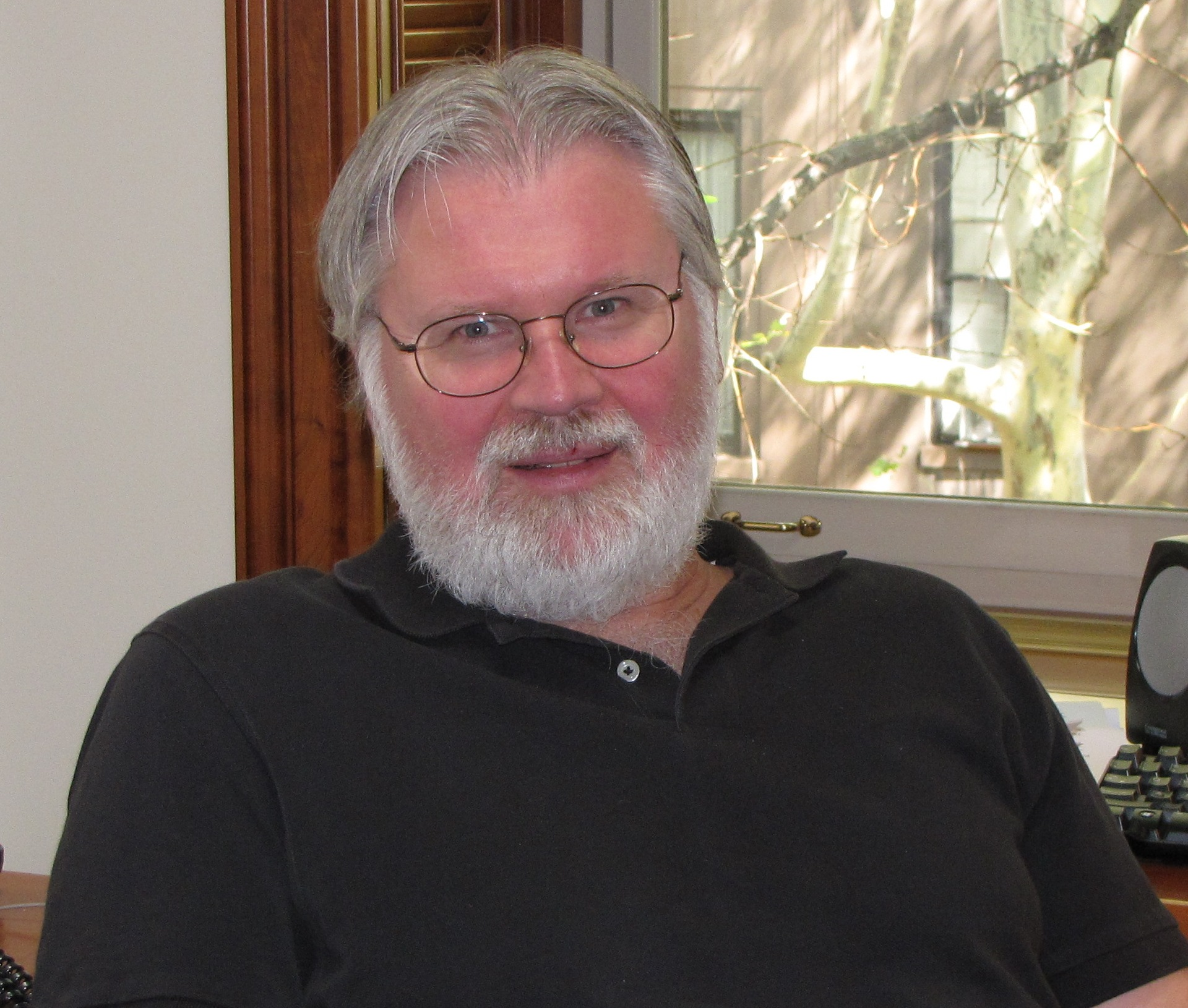 Photo of Douglas Massey with grey hair, beard, glasses, and black shirt.