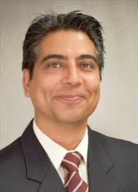 Headshot of Yubraj Acharya with short dark hair, white shirt, red and white striped tie, and gray jacket.