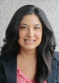 Headshot of Selena Ortiz with long black hair, pink blouse, and black jacket.