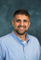 Headshot of Neil Mehta with short dark hair and blue button down shirt.