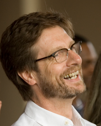 Headshot of Richard Wright with brown hair, beard, glasses, and white shirt.