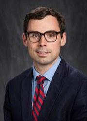 Headshot of Brian Theide with black hair, glasses, blue shirt, red and blue striped tie, and dark blue jacket.