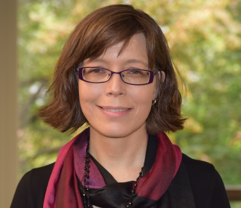 Headshot of Emily with brown hair, glasses, black blouse, and maroon scarf.