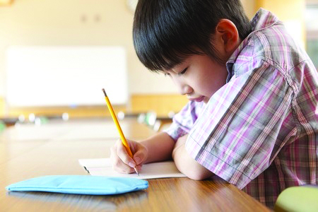 Young Asian boy studying.