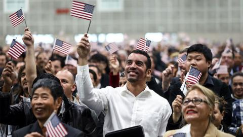 A gathering of immigrants waving small American flags.