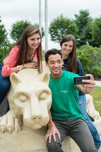 Three students posing for a picture at the Nittany Lion Shrine.