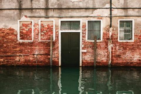 Photo of a brick building with a flooded street.