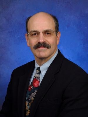 Headshot of Vernon Chinchilli with mustache, glasses, light blue shirt, multi-colored tie, and black jacket.