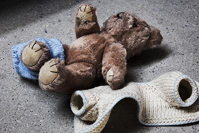 Photo of a teddy bear with its discarded sweater next to it.