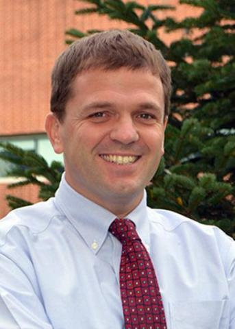 Headshot of Chris Fowler with short brown hair, white shirt, and red tie.
