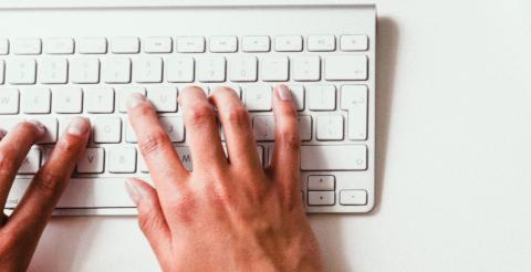 Photo of two hands typing on a keyboard.