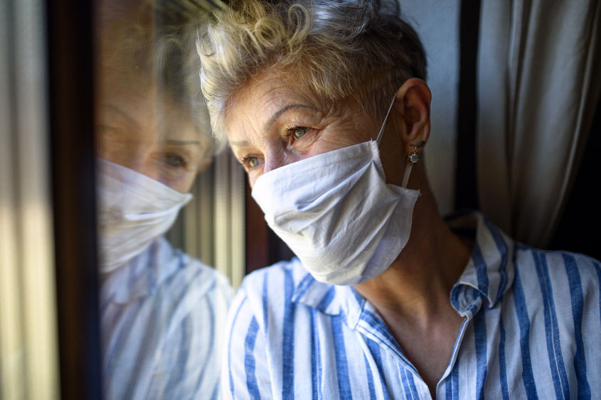 Senior woman with mask and blue shirt looking out window