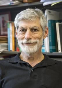 Headshot of Eric Plutzer in front of a book shelf with grey hair and beard wearing a black, collared shirt.