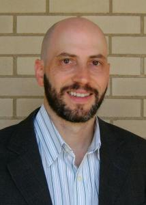 Headshot of John Iceland in front of brick wall wearing a striped-dress shirt and a suit jacket.