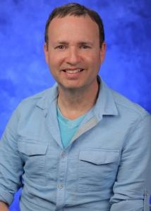 Headshot of Joshua Muscat in front of a blue background with short dark hair wearing a light blue button-up.