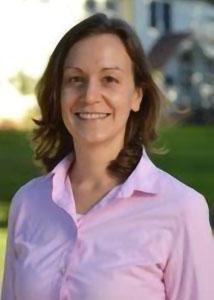 Headshot of Kathleen Sexsmith outsidewith long brown hair wearing a pink collared shirt.