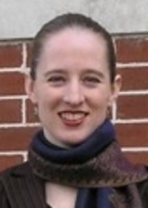 Headshot of Mary Shenk in front of a brick wall with hair pulled back wearing a scarf.