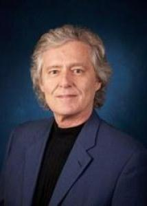 Headshot of Paul with gray hair, black shirt, and navy jacket.