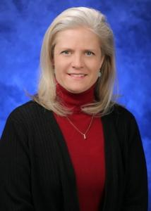 Headshot of Robin Wilson in front of a blue background with long blonde hair wearing a red turtle neck.