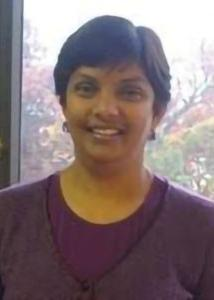 Headshot of Rukmalie Thalani Jayakody with short, dark hair wearing a purple top and statement earrings.
