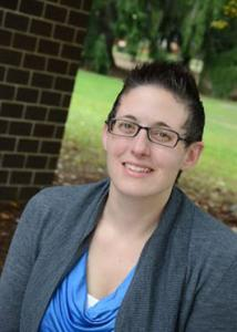 Headshot of Samantha Tornello outside with short, brown hair and glasses wearing a blue top with a grey jacket.