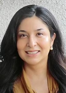 Headshot of Selena Ortiz with long dark hair wearing earrings and an orangish brown top.