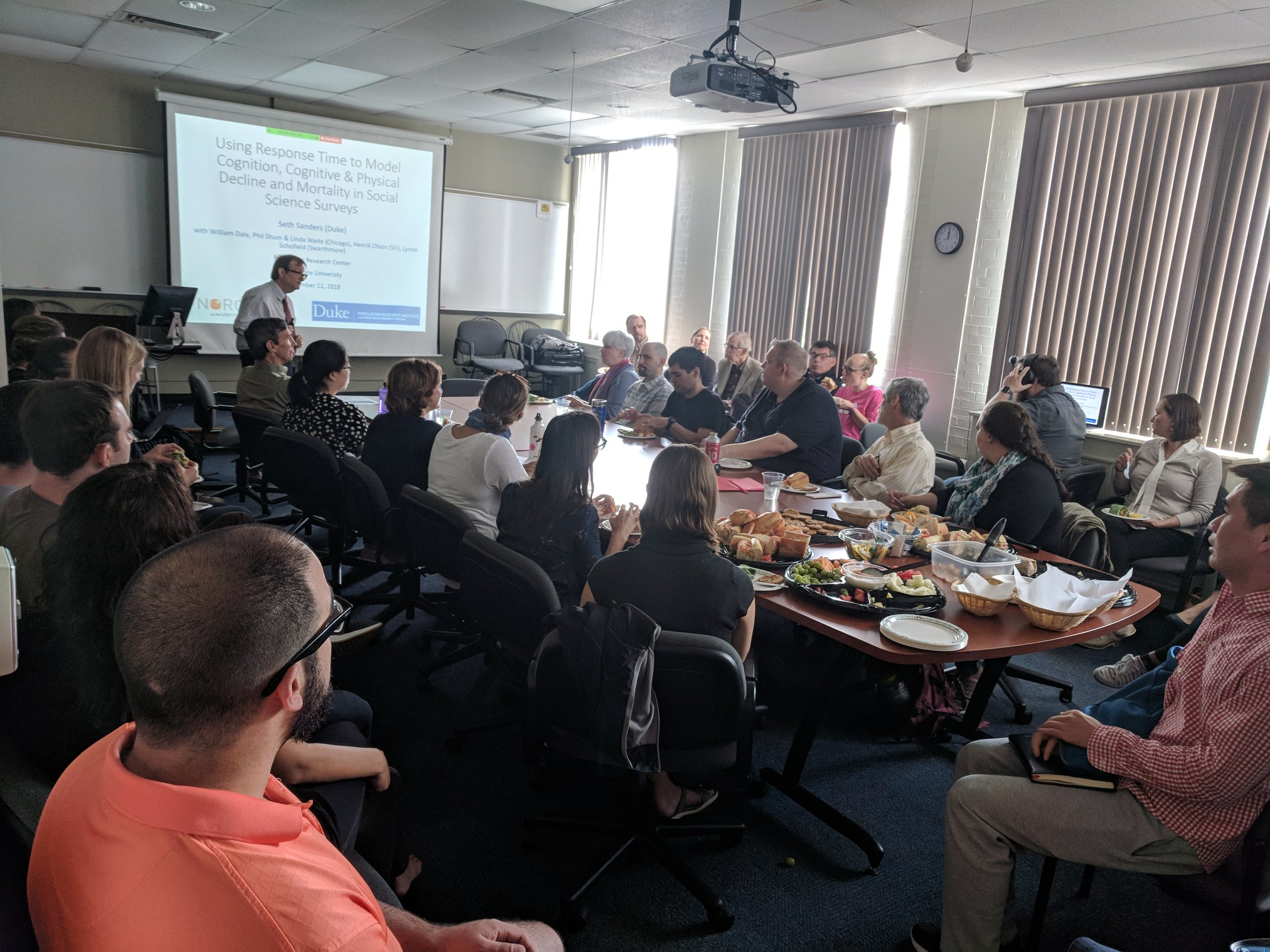 Photo taken during a Brown Bag presentation with a presenter showing a PowerPoint, a room full of people listening, and provided food on the table.